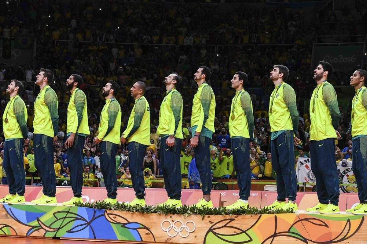 Seleção no pódio cantando o hino nacional - Reprodução/CBV
